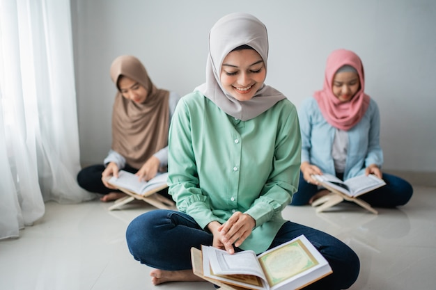 Tres mujeres jóvenes con hiyab leen el libro sagrado del corán