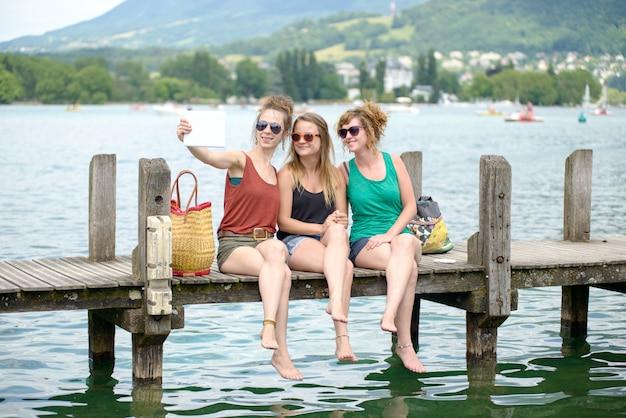 Tres mujeres jóvenes en la playa con su teléfono