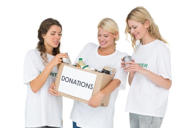 Tres mujeres jóvenes sonrientes con caja de donación
