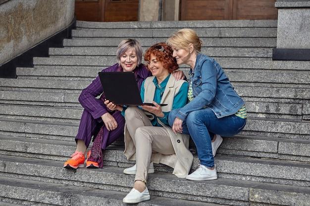 Tres mujeres mayores sonrientes con ordenador portátil se sientan en pasos a la entrada de un edificio europeo antiguo.