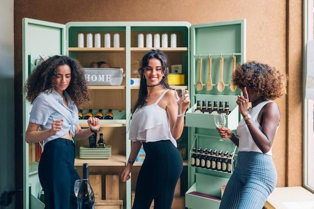 Tres mujeres multirraciales bebiendo y bailando en un pub moderno