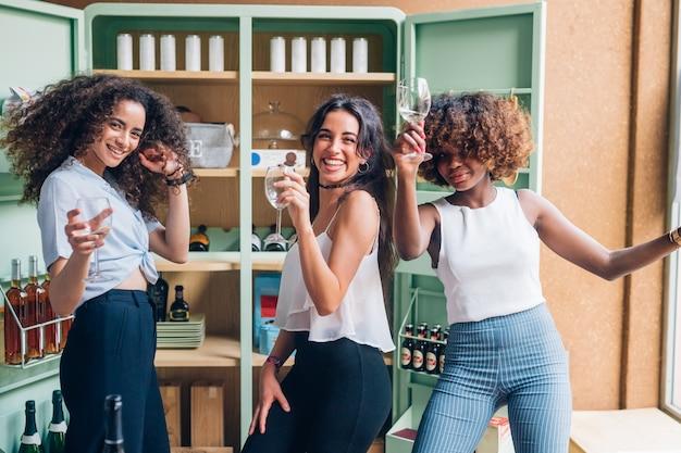 Tres mujeres multirraciales divirtiéndose y bailando en un pub moderno