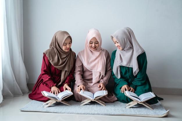 Tres mujeres musulmanas asiáticas leen y aprenden juntas el libro sagrado del al-quran