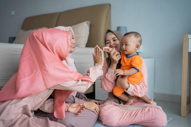 Tres mujeres musulmanas disfrutan jugando con un niño pequeño cuando se sientan en el suelo