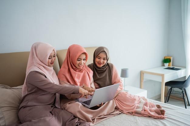Tres mujeres musulmanas que usan una computadora portátil para ver información actualizada de noticias