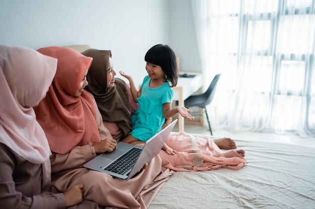 Tres mujeres musulmanas y su hija usando una computadora portátil para ver información actualizada