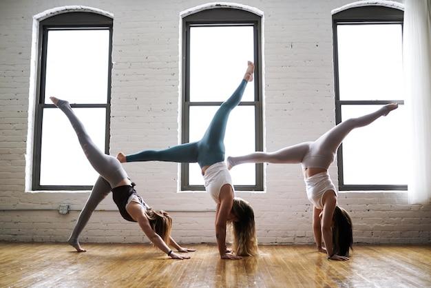 Tres mujeres practicando yoga vistiendo trajes ajustados de yoga en una habitación grande