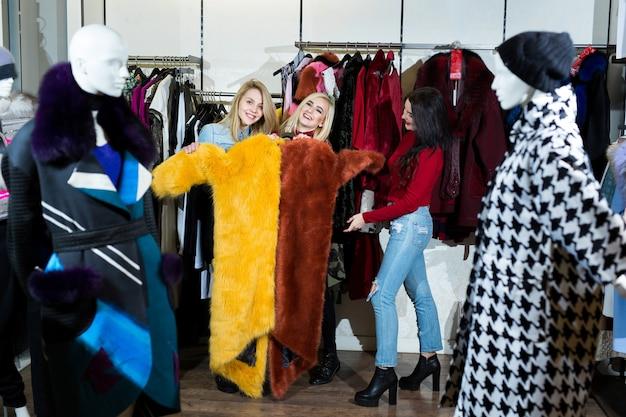 Tres mujeres probándose un abrigo de piel en la tienda