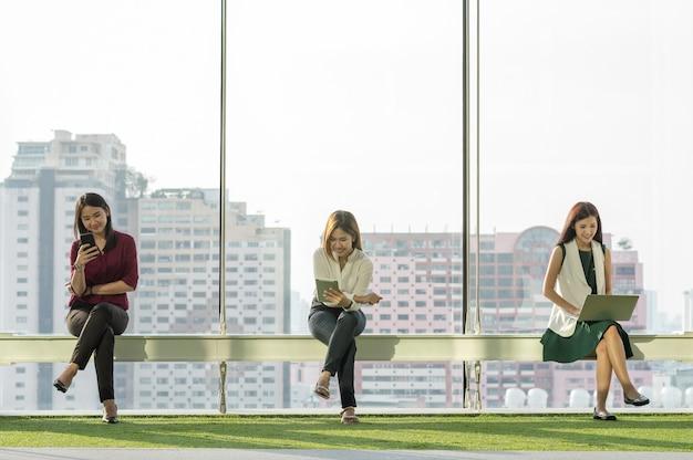 Tres mujeres que usan redes sociales cada equipo de tecnología en la moderna oficina creativa al lado del