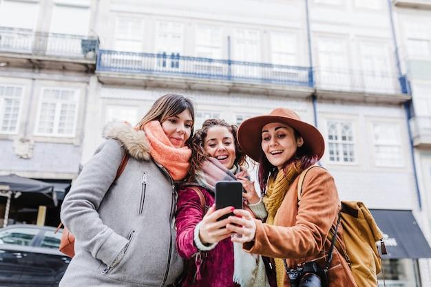 Tres mujeres recorriendo las vistas de porto y tomando fotografías con el teléfono móvil. concepto de viaje y amistad