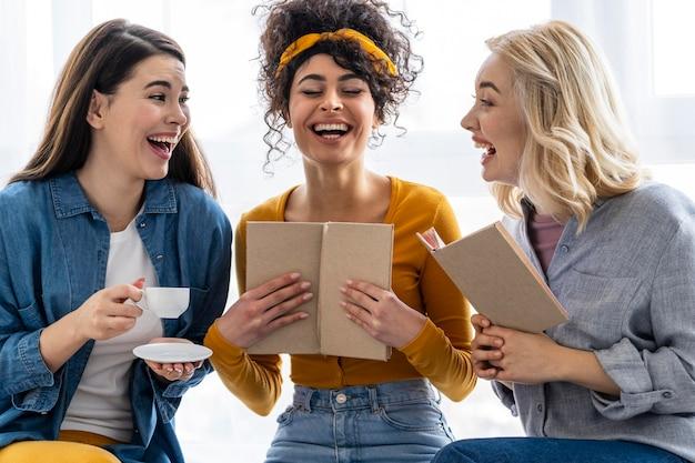 Tres mujeres riendo junto con libro