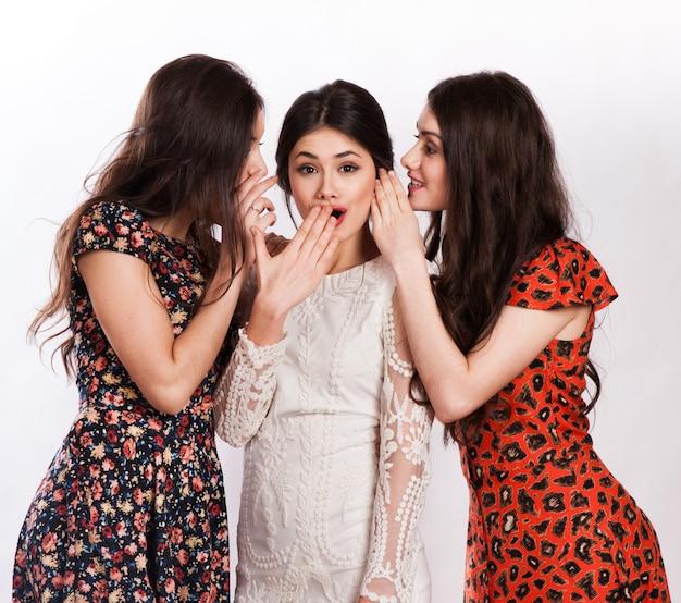 Tres mujeres sonrientes susurrando chismes