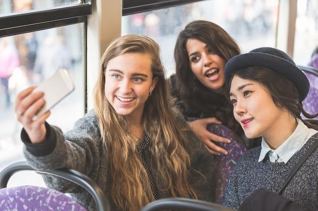 Tres mujeres tomando una autofoto en el autobús.