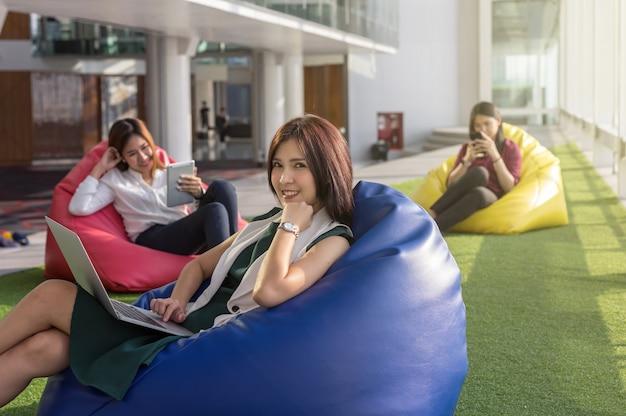 Tres mujeres usan redes sociales cada equipo de tecnología en la moderna oficina creativa