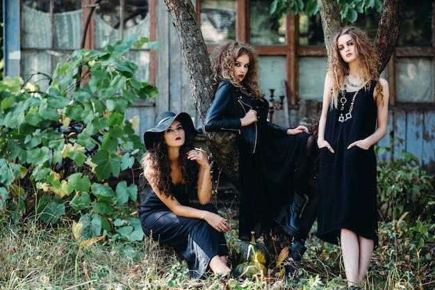 Tres mujeres vintage como brujas, posan frente a un edificio abandonado en la víspera de halloween