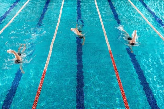 Tres nadadores varones corriendo uno contra el otro