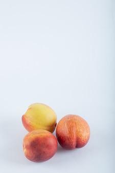 Tres nectarinas frescas en blanco.