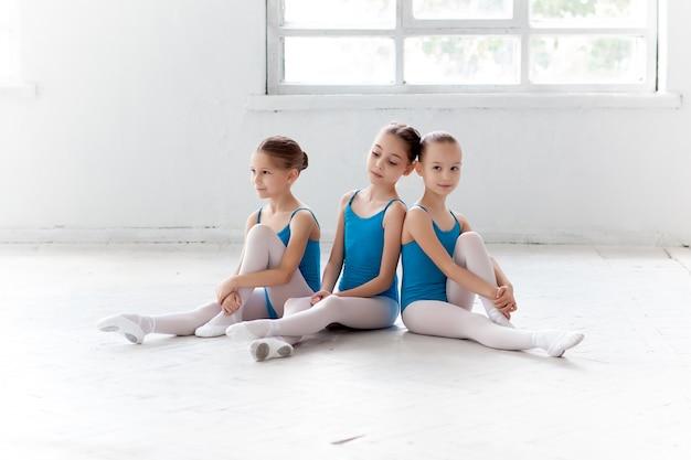 Tres niñas de ballet sentado y posando juntos