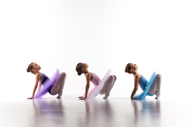 Tres niñas de ballet sentado en tutú y posando juntos