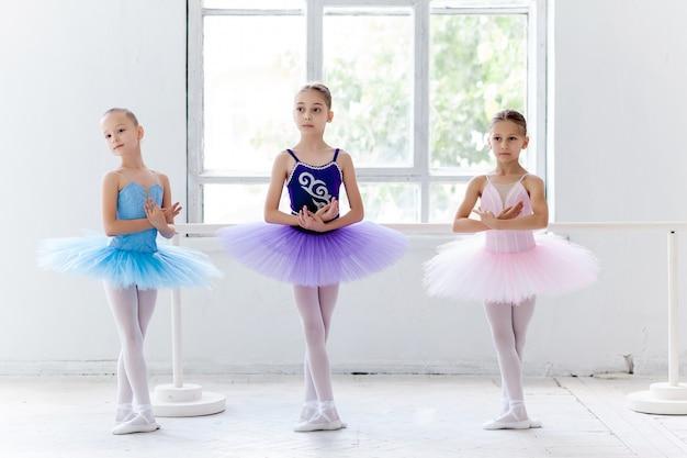 Tres niñas de ballet en tutú y posando juntas