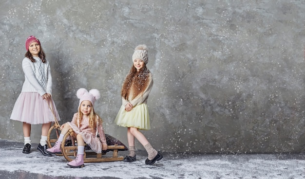 Tres niñas se divierten jugando y en trineo, los niños hermosos disfrutan la llegada del invierno. rusia, sverdlovsk, 18 de noviembre de 2018