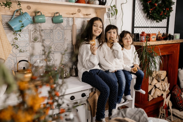 Tres niñas encantadoras vestidas con suéteres blancos y pantalones vaqueros azules juegan en una cocina antigua.