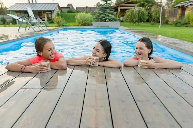 Tres niñas felices con bebidas en la fiesta de verano en la piscina
