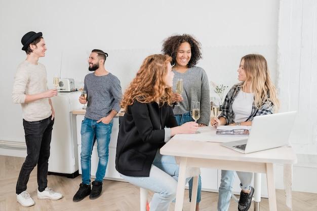 Tres niñas felices interculturales con champaña charlando