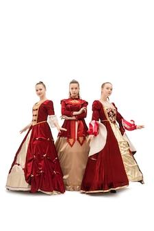 Tres niñas en hermosos vestidos rojos de la reina aislado disparo de longitud completa