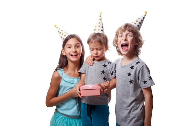 Tres niños alegres felices con sombreros de papel festivos celebrando la fiesta de cumpleaños