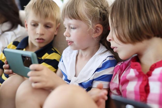 Tres niños están sentados en el sofá y miran la pantalla del teléfono inteligente.