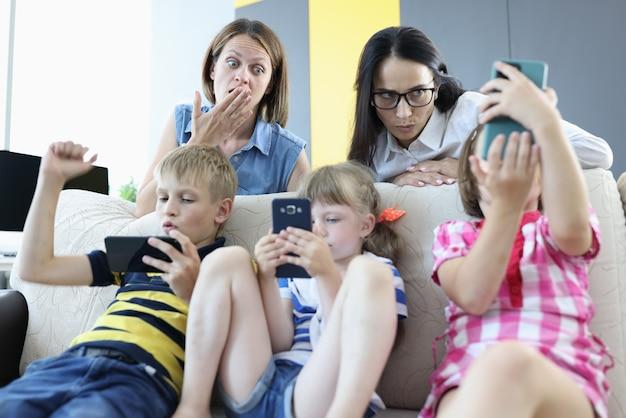 Tres niños están sentados en el sofá con teléfonos inteligentes en sus manos, jugando juegos en línea desde el respaldo del sofá, dos mujeres están de pie y mirando asustadas a la pantalla del teléfono.