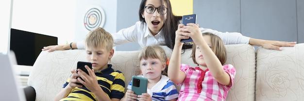 Tres niños están sentados en el sofá con teléfonos inteligentes en sus manos