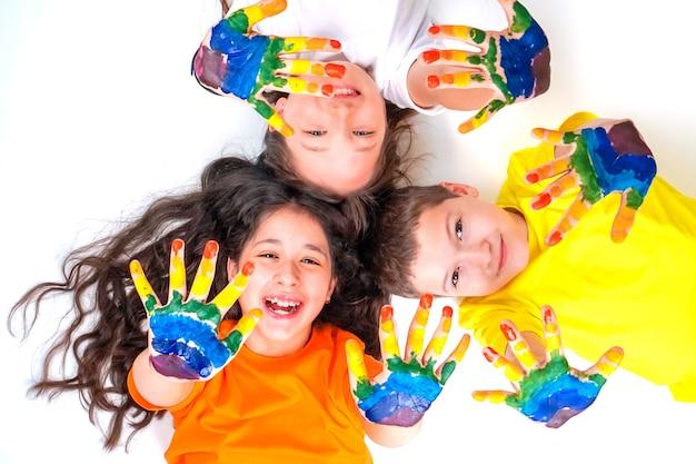 Tres niños felices y sonrientes están mirando a la cámara y extendiendo sus manos en pinturas.