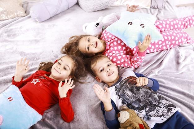 Tres niños felices yacen sobre la manta vestidos con ropa de dormir