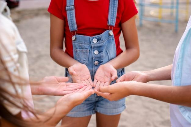 Tres niños haciendo tomar sus manos juntas