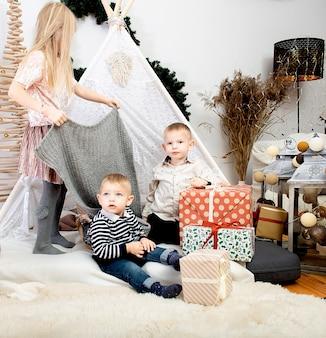 Tres niños niños jugando entre cajas de regalo de navidad en una casa decorada ¡feliz navidad y felices fiestas!