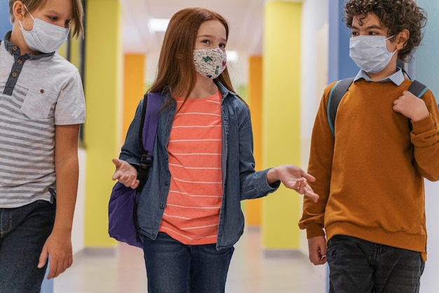 Tres niños en el pasillo de la escuela con máscaras médicas.