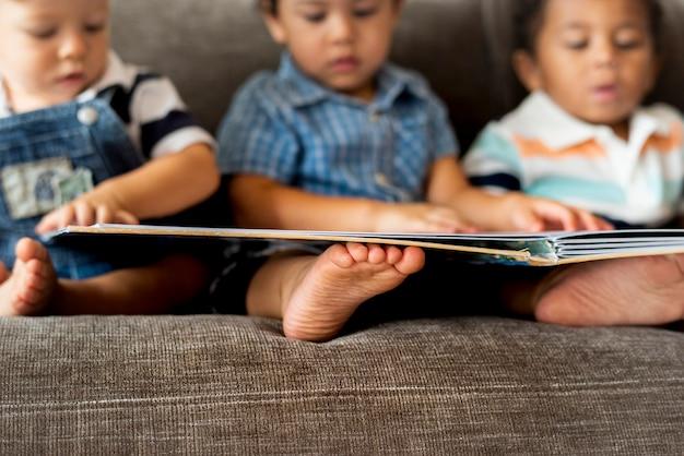 Tres niños pequeños leyendo un libro en un sofá