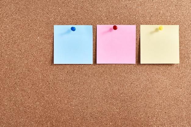 Tres notas adhesivas clavadas en el tablero de corcho. concepto de planificación y lluvia de ideas
