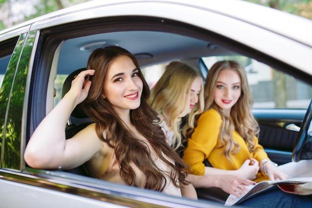 Tres novias jóvenes viajando en un automóvil.