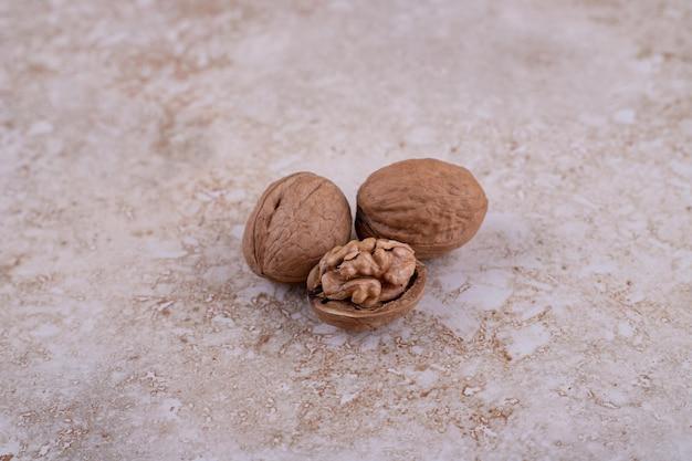 Tres nueces deliciosas saludables sobre fondo de mármol.