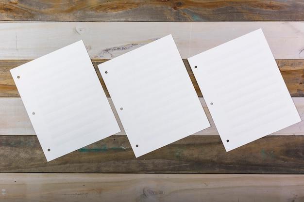 Tres páginas musicales en blanco pegadas en pared de madera.