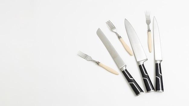 Tres pares de cuchillos de cocina, tenedores con mangos negros. fondo blanco flatlay
