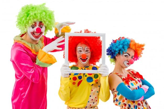 Tres payasos juguetones sosteniendo haciendo caras divertidas.