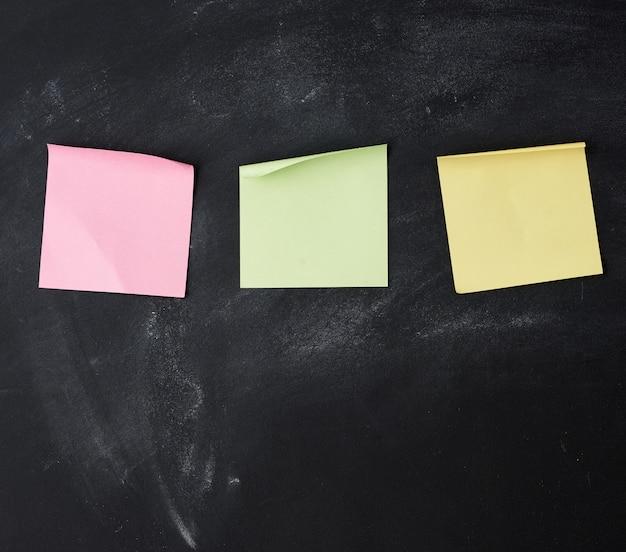 Tres pegatinas cuadradas multicolores de papel en blanco