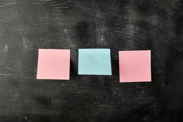 Tres pegatinas de papel en blanco están pegadas a una tabla de madera negra