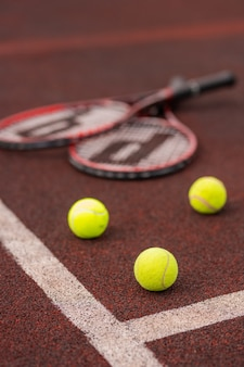 Tres pelotas de tenis por líneas blancas cruzadas en la cancha con dos raquetas