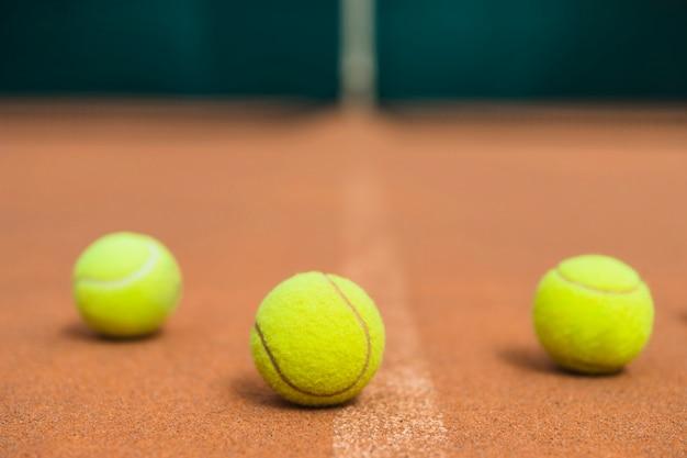 Tres pelotas de tenis verdes en la cancha de tenis.