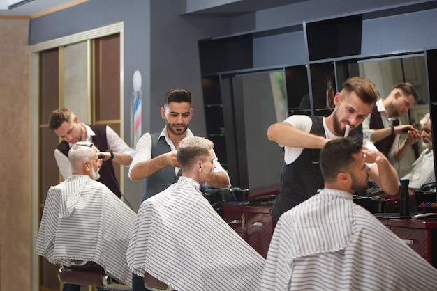 Tres peluqueros profesionales que recortan, cortan y peinan el cabello de clientes masculinos.
